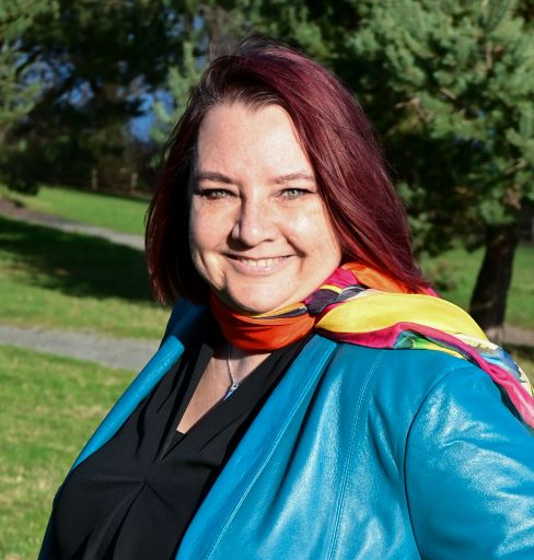 Headshot of white woman with red hair wearing a colorful scarf and a teal jacket. Trees and grass in the background.